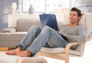 8398164-Goodlooking-young-man-relaxing-at-home-in-armchair-sitting-in-living-room-with-laptop-computer-smili-Stock-Photo